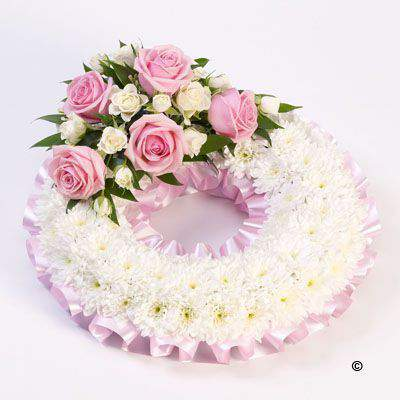 A classic circular wreath covered with a mass of white double spray chrysanthemums and finished with a pink and white spray of roses and spray roses and finished with a pink ribbon trim.