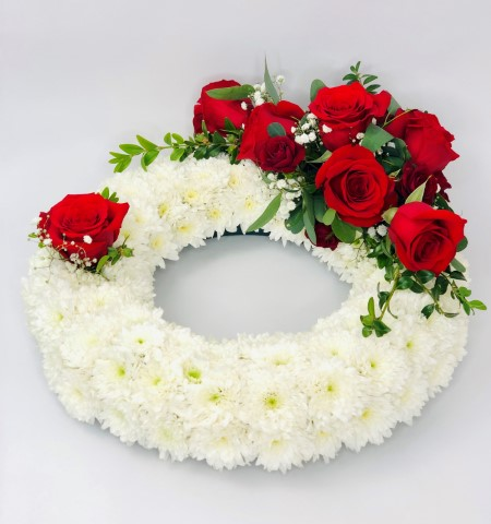 A classic circular wreath covered with a mass of white double spray chrysanthemums and finished with a red and white spray of roses and spray roses and finished with a red ribbon trim.