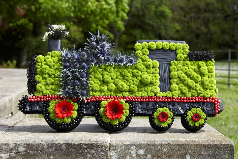 This train tribute is covered in a bed of fresh white double spray chrysanthemums and yellow spray carnations and finished with gold - red - yellow and black spray colours.