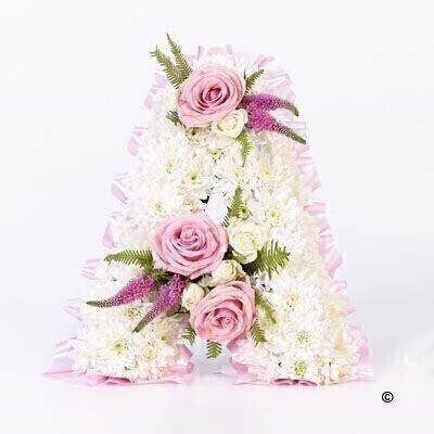 A tribute letter made using a mass of white double spray chrysanthemums edged with fern and leather leaf - with feature sprays of pink roses - white spray roses and pink veronica.