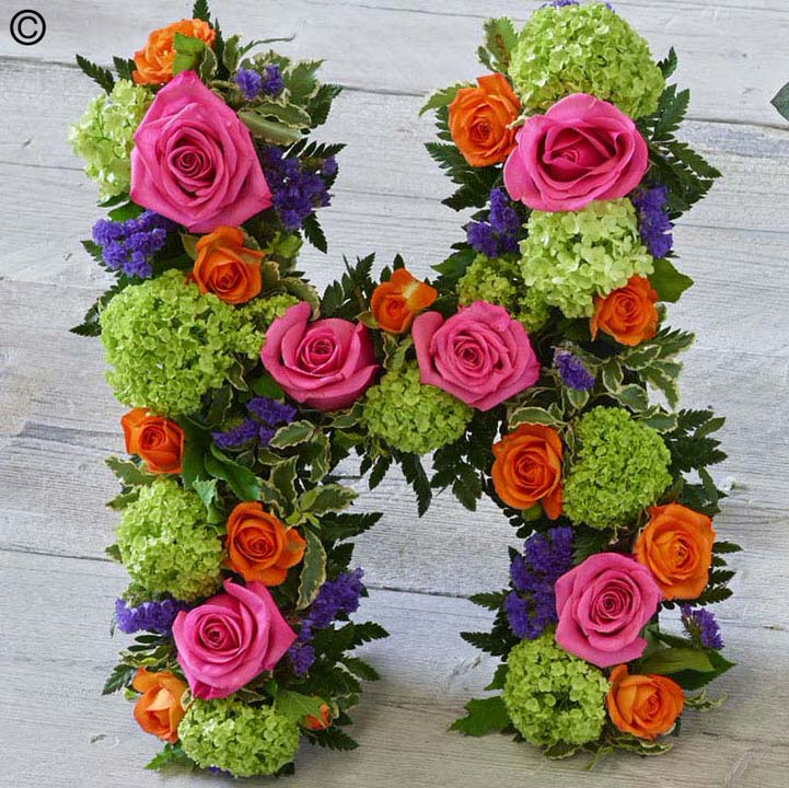A colourful tribute letter of your choice is created using cerise short Stem roses - orange spray carnations - lime green spray chrysanthemums and blue statice - trimmed with leather leaf and pittosporum.