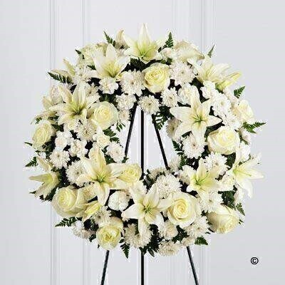 Pure white roses - Asiatic Lily - carnations and spray chrysanthemums are beautifully arranged to form an elegant wreath accented wth lush and vibrant greens. Displayed on a wire easel - this stunning tribute is a wonderful symbol of eternal life.