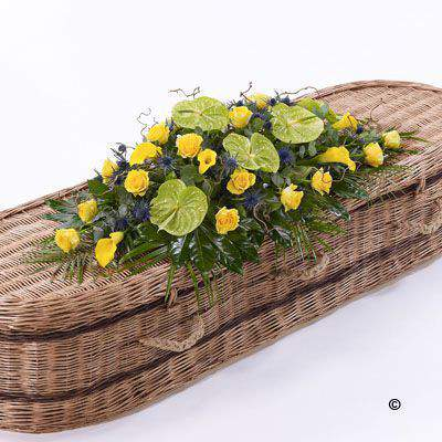 Yellow calla Lily and large-headed Rose are complemented by lime green anthuriums - blue eryngium and foliages including palm and aralia leaves. Twisted willow Stems are used to finish this stunning Casket Spray.