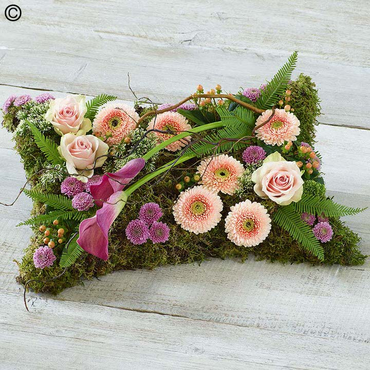 This pillow-shaped design has a woodland theme and includes pink large-headed roses - germini and spray chrysanthemums along with calla Lily and twisted hazel amongst an array of greenery.