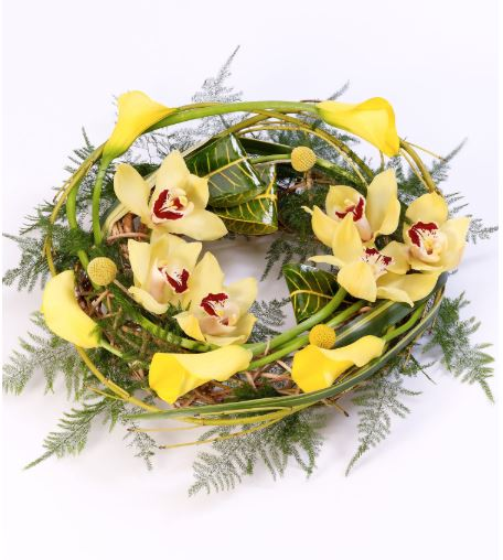 Yellow calla Lily and cymbidium orchids are entwined with cornus Stems - craspedia and asparagus fern around a circular willow frame to create this woodland wreath.