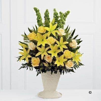 Yellow Asiatic Lily - roses and solidago are offset by cream roses - molucella - palm fronds and choice foliage to create a vibrant display. Arranged in a large papier mache urn - this beautiful display will make a lovely addition to the service.