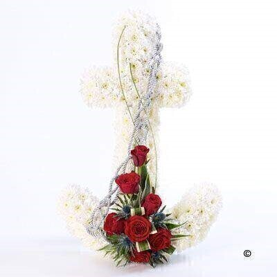An anchor shaped design using a mass of white double spray chrysanthemums with a feature spray of red short Stem roses and a contrasting blue eryngium. The tribute is finished with green foliage and a silver cord.