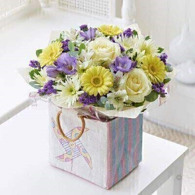 THIS ARRANGEMENT IS DONE IN FLORAL FOAM AND COMES PRE ARRANGED IN THE BAG FOR DISPLAY We've chosen this selection of pretty flowers in cool shades of lemon and lilac to celebrate the arrival of a bouncing baby boy. Carefully arranged and beautifully presented in this cute bag this gift is a charming gift choice for any new parent. Featuring white alstroemeria purple freesia lemon germini white large headed rose white spray chrysanthemum and a purple statice with pittosporum and eucalyptus presented in a candy-striped jute bag with windmill motif. Approximate Product Dimensions: Standard Height: 32cm Width: 24cm Plus Height: 34cm Width: 26cm