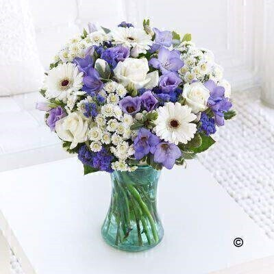 Large Version of our Baby Boy Vase. andnbsp;A new little boy has arrived and itandrsquo;s time to celebrate! Weandrsquo;ve chosen a beautiful selection of fresh blooms in cool lilac and blue shades partnered with crisp white to create a stunning vase of flowers that they are sure to love. Featuring white spray chrysanthemums - purple statice - white germini - lilac lisianthus - white large headed rose - and purple freesia with salal and pittosporum - arranged in a blue swirl Nigella vase and trimmed with a blue button heart tag.