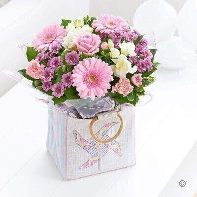 THIS ARRANGEMENT IS DONE IN FLORAL FOAM AND COMES PRE ARRANGED IN THE BAG FOR DISPLAY Let them know how delighted you are to hear of the safe arrival of a beautiful baby girl. This pretty gift bag is full of stunning fresh flowers in exquisite shades of pink and cream. It's simply perfect — just like she is. Featuring lilac freesia pink germini a pink large headed rose white spray chrysanthemums and pink alstroemeria with eucalyptus and pittosporum presented in a candy-striped jute bag with windmill motif. Approximate Product Dimensions: Standard Height: 35cm Width: 24cm Plus Height: 35cm Width: 26cm