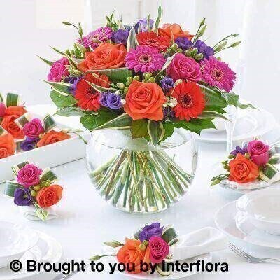 Vibrant Flowers – Table Decoration<br><br> Liverpool Flower Delivery<br><br> We offer advanced booking flower delivery same day flower delivery 3 hour Flower delivery guaranteed AM PM or Evening Flower Delivery and we are now offering Sunday Flower Delivery. .<br><br> <ul><li>Hand arranged by our florists</li><li> To give the best occasionally we may make substitutes</li><li> 7 days freshness guarantee only on globe vase </li><li> Approximate dimensions Vase 32x32 Napkin decorations 13x11cm</li><li> This product is available for delivery throughout the UK</li></ul><br><br>  THIS PRODUCT IS A TEMPORARY TABLE DECORATION  ONCE MADE THE FLOWERS ARE NOT DRINKING  SO LONGEVITY OF FLOWERS BEYOND THE WEDDING OR EVENT CAN NOT BE GUARANTEED.  WE RECOMMEND DELIVERY TO BE AROUND 2 HOURS BEFORE THE EVENT SO PLEASE STATE TIME OF THE EVENT IN THE SPECIAL DELIVERY INSTRUCTIONS Opt for the complete package and choose the ultimate in table décor. Our expertly arranged designer flower globe makes a radiant centrepiece in vivid pink  orange and purple. Individually crafted matching floral napkin decorations look amazing and will charm your guests too.<br><br>  Featuring 3 dark red germini  3 cerise germini  2 green hypericum  3 blue lisianthus  2 cerise large headed roses and 3 orange large headed roses with folded aspidistra leaves  variegated dracaena and salal presented in a large globe glass vase accompanied with 6 napkin decorations featuring green hypericum  blue lisianthus  2 large headed roses (cerise and orange) and green dracaena trimmed with natural raffia.<br><br> The best florist in Liverpool<b><b>Come to Booker Flowers and Gifts Liverpool for your Beautiful Flowers and Plants if you really want to spoil we also have a great range of Wines Champagne Balloons Vases and Chocolates that can be delivered with your flowers. To see the full range see our extras section. You can trust Booker Flowers and Gifts can deliver the very best for you
