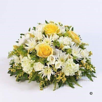 A classic selection in lemon and white including large-headed roses - freesias - lisianthus and spray chrysanthemums presented in a posy design.