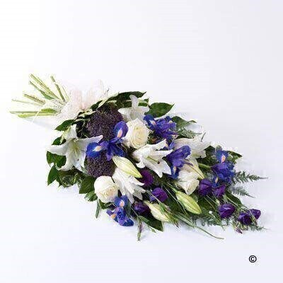The soft blue shades of iris are complemented by white Oriental liles - white large-headed roses and blue lisianthus in this classic sheaf - which is tied together with a cream ribbon.