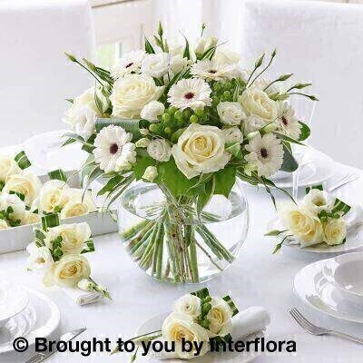 White Flowers – Table Decoration<br><br> Liverpool Flower Delivery<br><br> We offer advanced booking flower delivery same day flower delivery 3 hour Flower delivery guaranteed AM PM or Evening Flower Delivery and we are now offering Sunday Flower Delivery. .<br><br> <ul><li>Hand arranged by our florists</li><li> To give the best occasionally we may make substitutes</li><li> 7 days freshness guarantee only on globe vase </li><li> Approximate dimensions Vase 32x32 Napkin decorations 13x11cm</li><li> This product is available for delivery throughout the UK</li></ul><br><br>  THIS PRODUCT IS A TEMPORARY TABLE DECORATION  ONCE MADE THE FLOWERS ARE NOT DRINKING  SO LONGEVITY OF FLOWERS BEYOND THE WEDDING OR EVENT CAN NOT BE GUARANTEED.  WE RECOMMEND DELIVERY TO BE AROUND 2 HOURS BEFORE THE EVENT SO PLEASE STATE TIME OF THE EVENT IN THE SPECIAL DELIVERY INSTRUCTIONS Style your table with the ultimate in natural elegance. Our package includes a set of six hand-crafted flower napkin decorations plus a luxurious designer vase arrangement in a stunning glass globe.<br><br>  Featuring 6 white germini  2 green hypericum  3 white lisianthus and 5 white large headed roses with folded aspidistra leaves  dracaena and salal presented in a large globe glass vase accompanied with 6 napkin decorations featuring green hypericum  white lisianthus and 2 white large headed roses with variegated dracaena  trimmed with natural raffia.<br><br> The best florist in Liverpool<b><b>Come to Booker Flowers and Gifts Liverpool for your Beautiful Flowers and Plants if you really want to spoil we also have a great range of Wines Champagne Balloons Vases and Chocolates that can be delivered with your flowers. To see the full range see our extras section. You can trust Booker Flowers and Gifts can deliver the very best for you