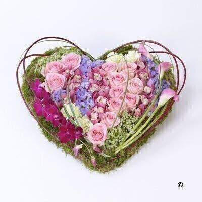 This heart-shaped design including large-headed roses - carnations and cymbidium and dendrobium orchids is given a contemporary feel with sweeping pink calla Lily - cornus and steel grass.