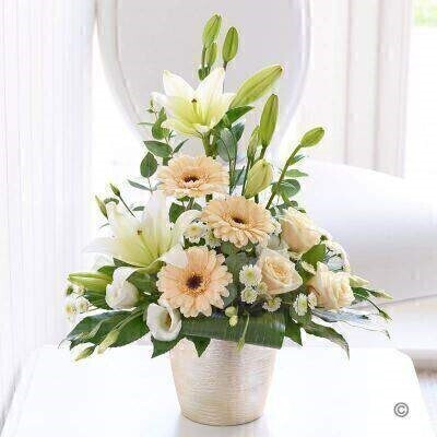 If you're looking for a chic elegant gift that has a timeless beauty all of its own this arrangement is simply perfect. Pristine white lilies are the stars of this design complemented beautifully with exquisite cream roses and germini in the softest shade of warm peach.<br><br>Featuring 2 white Asiatic lilies 3 cream large headed roses 3 peach germini a white spray chrysanthemum and a white lisianthus with eucalyptus aralia and rolled aspidistra leaves presented in a ceramic vase with metallic textured finish.<br><br>This product contains 10 stems.
