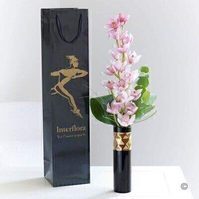 This exquisite pink orchid is perfectly presented in a stylish black and gold vase. It's such an elegant gift; with just a little added foliage to complement the stem of the exotic cymbidium orchid. This vase arrangement features a pink mini cymbidium orchid with aspidistra leaf and bear grass - delivered in a gift bag.