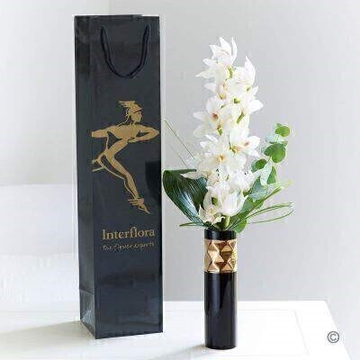 This exquisite white orchid is perfectly presented in a stylish black and gold vase. It's such an elegant gift; with just a little added foliage to complement the stem of the exotic cymbidium orchid. This vase arrangement features a white mini cymbidium orchid with aspidistra leaf and bear grass - delivered in an Interflora gift bag.