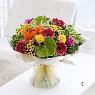 For a gift that is a little bit different - this brightly coloured bouquet is the perfect choice. The vibrant orange lilies look amazing set against lime green anthuriums - and the addition of yellow and cerise creates a really zesty mix that is certain to impress. Featuring green anthuriums - cerise carnations - orange Asiatic lilies - yellow large-headed roses - cerise gerbera and yellow spray chrysanthemums - with pittosporum and salal - gift-wrapped and trimmed with a gold voile ribbon.