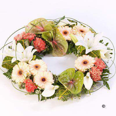 An elegant wreath featuring an exotic mix of anthuriums - calla Lily - Gerbera - Lily and carnations in green - orange and white. Tropical foliage and looped steel grass give it a contemporary feel.