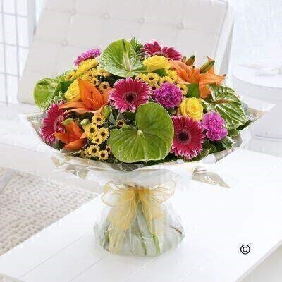 Large version of our Exotic Mixed Hand-Tied. andnbsp;Aandnbsp;gift that is a little bit different - this brightly coloured bouquet is the perfect choice. The vibrant orange lilies look amazing set against lime green anthuriums - and the addition of yellow and cerise creates a really zesty mix that is certain to impress. Featuring green anthuriums - cerise carnations - orange Asiatic lilies - yellow large-headed roses - cerise gerbera and yellow spray chrysanthemums - with pittosporum and salal - gift-wrapped and trimmed with a gold voile ribbon.