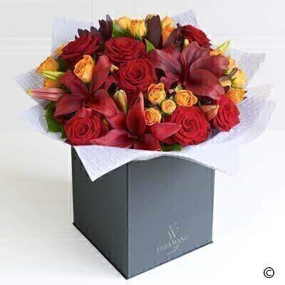 The Large Version on Vera Wang Sheer Opulence. andnbsp;A celebration of the warmest - most vibrant natural colours - this magnificent Vera Wang bouquet is a striking statement piece. The scarlet - large-headed roses pair with the crimson red Asiatic lilies perfectly. Adding rich burgundy leucadendron and orange spray roses creates a vibrant mix of colour and a very opulent gift.