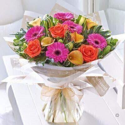 THIS PRODUCT COMES HAND ARRANGED AND GIFT WRAPPED IN A WATER BUBBLE PRESENTED IN A BOX The giving of fresh flowers is all about making an impact and this vibrant design certainly does so in style. Radiant in shades of hot pink bright orange and rich gold this is an impressive showstopper gift of exotic colours and luxurious varieties. Simply stunning! Featuring 3 orange large headed roses 5 cerise gerbera and 5 orange calla lilies hand-tied with pittosporum salal philodendron and phormium leaves wrapped and trimmed with Gold Wire Edge Organza Ribbon. This product contains 13 stems.