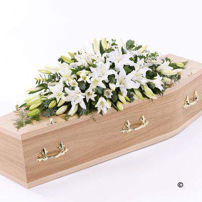 A blanket of white Oriental Lily is beautifully complemented by an array of luxurious deep green leaves to create this simple but striking casket spray.