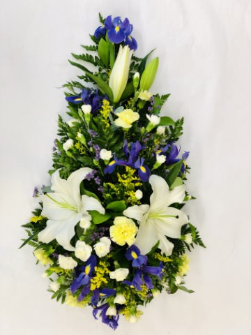 Asiatic Lily and carnations are presented with irises - spray carnations and choice foliage to create this lemon and blue teardrop spray.