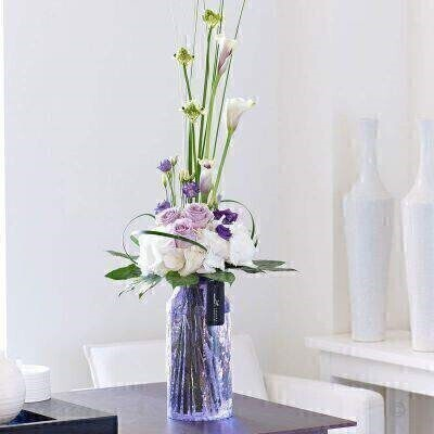 Vase IncludedThis beautiful tall design of white lilac and purple shades is sure to make a lasting impression on someone special. The purple crackled vase compliments the flowers wonderfully and gleams in the light from all angles.This beautiful tall design of white lilac and purple shades is sure to make a lasting impression on someone special. The purple crackled vase compliments the flowers wonderfully and gleams in the light from all angles.his product contains 12 stemsApproximate Product Dimensions: Height: 77cm Width: 26cm
