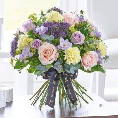 THIS PRODUCT COMES HAND ARRANGED AND GIFT WRAPPED IN A WATER BUBBLE PRESENTED IN A BOX.<br><br>This exquisite hand-tied draws on a colour palette of pretty pastels ranging from pale pink and lilac to lavender and cream. It's a naturally stylish yet informal display that looks particularly feminine — and these stunning roses really add to the luxuriousness of this generous gift.<br><br>Featuring St Cream carnations pale pink Sweet Avalanche large headed roses lilac Ocean Song large headed roses lilac Blue Moon freesia and lilac Blue Lane trachelium with bupleurum eucalyptus and salal expertly hand-tied and presented in luxurious packaging for maximum impact when your gift is delivered.<br><br>This product contains 21 stems.<br><br>Approximate Product Dimensions:<br><br>Height: 40cm Width: 38cm