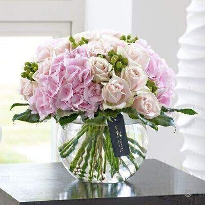 Vase IncludedThis heavenly display of luxurious Sweet Avalanches roses and classically stunning pink hydrangea is perhaps the epitome of natural beauty. We adore these delicate pink shades for their femininity and elegance. This wonderful gift choice will assume pride of place perfectly.Featuring Verena pink hydrangea pink Sweet Avalanche large headed roses and Selva green hypericum with aralia leaves expertly tied with lily grass and arranged in a swirl glass globe finished with luxury gold and black gift wrapping for maximum impact when your gift is delivered.This product contains 23 stems.Approximate Product Dimensions: Height: 30cm Width: 32cm