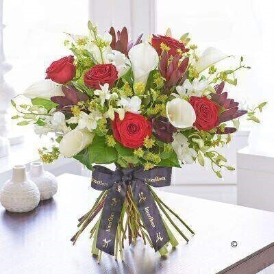 THIS PRODUCT COMES HAND ARRANGED AND GIFT WRAPPED IN A WATER BUBBLE PRESENTED IN A BOX.<br><br>This is a beautifully conceived designer bouquet. With its cherry red roses and immaculate white calla lilies the contrast is dramatic — and impressive. Delicate white dendrobium orchids add gorgeous detail too. A stunning celebration of the very finest quality flowers.<br><br>Featuring white Avalanche calla lilies white Madame Pomp dendrobium orchid heads red Naomi large headed roses and red Secession leucadendron with bupleurum and salal expertly hand-tied and presented in luxurious packaging for maximum impact when your gift is delivered.<br><br>This product contains 25 stems.<br><br>Approximate Product Dimensions:<br><br>Height: 45cm Width: 46cm