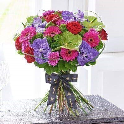 THIS PRODUCT COMES HAND ARRANGED AND GIFT WRAPPED IN A WATER BUBBLE PRESENTED IN A BOX.<br><br>This exotic bouquet is perfect for a special occasion. Radiant orchid blooms in a wonderfully rich shade of deep purple are the height of luxury — and notice how their glorious colour is enhanced with contrasting lime ruby and cerise flowers. A magnificent gift.<br><br>Featuring Blue Magic Vanda orchid heads in individual hydrating tubes green Midori anthurium cerise St Farida carnations cerise Whisper germini red Naomi large headed roses and green Feeling Free spray chrysanthemums with steel grass and salal expertly hand-tied and presented in luxurious packaging for maximum impact when your gift is delivered.<br><br>This product contains 26 stems.<br><br>Approximate Product Dimensions:<br><br>Height: 45cm Width: 45cm