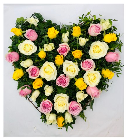 Large-headed roses in pink - yellow and cream and short-Stem roses in white are nestled into an solid heart shape amongst asparagus fern and pittosporum.