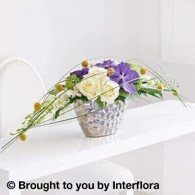 Purple and Yellow Flowers – Modern Flowers<br><br> Liverpool Flower Delivery<br><br> We offer advanced booking flower delivery same day flower delivery 3 hour Flower delivery guaranteed AM PM or Evening Flower Delivery and we are now offering Sunday Flower Delivery. .<br><br> <ul><li>Hand arranged by our florists</li><li> To give the best occasionally we may make substitutes</li><li> Our flowers backed by our 7 days freshness guarantee</li><li> Approximate dimensions 32x100cm</li><li> This product is available for delivery throughout the UK</li></ul><br><br>  THIS ARRANGMENT IS IN FLORAL FOAM AND COMES PRE ARRANGED IN CONTAINER This immaculately presented arrangement is designed as a streamlined statement piece. Bringing together the latest trends in floral sophistication  vibrant Vanda orchid heads contrast with blowsy roses and simple craspedia in a wide  free-flowing shape  interspersed with layers of ivory Dendrobium orchids and steel grass which form a natural canopy.<br><br>  Featuring 9 yellow craspedia  4 white dendrobium orchids  6 white large headed roses  3 Blue Vanda orchids and a green viburnum with folded aspidistra leaves  philodendron  steel grass and umbrella fern  presented in a silver dimple oval ceramic planter.<br><br> The best florist in Liverpool<b><b>Come to Booker Flowers and Gifts Liverpool for your Beautiful Flowers and Plants if you really want to spoil we also have a great range of Wines Champagne Balloons Vases and Chocolates that can be delivered with your flowers. To see the full range see our extras section. You can trust Booker Flowers and Gifts can deliver the very best for you