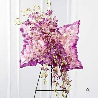 Light pink spray chrysanthemums - purple dendrobium orchids and lavender roses are beautifully arranged against a bed of purple and lavender satin to create a stunning presentation. Displayed on a wire easel - this arrangement bursts with grace and elegance