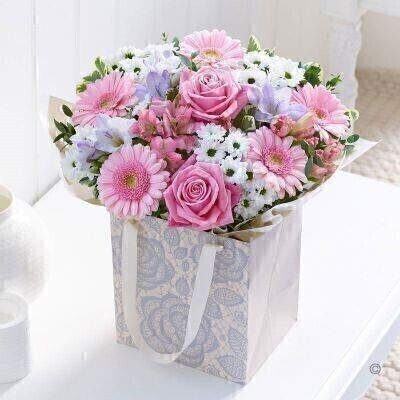 THIS ARRANGEMENT IS DONE IN FLORAL FOAM AND COMES PRE ARRANGED IN THE BAG FOR DISPLAY<br><br>This charming jute bag filled with pretty pink and white flowers makes a very feminine gift for someone special. The soft shades of pastel pink with fresh white look wonderful together. This is a lovely treat they'll be delighted to receive.<br><br>Featuring lilac freesia pink germini pink rose white spray chrysanthemums and pink alstroemeria with eucalyptus and pittosporum presented in a lace design gift bag.<br><br>Approximate Product Dimensions:<br><br>Standard<br><br>Height: 35cm Width: 24cm<br><br>Plus<br><br>Height: 35cm Width: 26cm