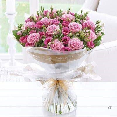 THIS PRODUCT COMES HAND ARRANGED AND GIFT WRAPPED IN A WATER BUBBLE PRESENTED IN A BOX Indulge her passion for pink with this ultra-feminine bouquet. We ve chosen classic roses for their enduring beauty and delicate lisianthus for extra detail. The soft pink shades of both varieties look wonderful together and are sure to prompt a smile of pure pleasure. Featuring pink lisianthus and pink large headed roses with salal and pittosporum wrapped and trimmed with a Gold Wire Edge Organza Ribbon.