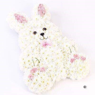 This sweet floral tribute in the shape of a rabbit features fresh white double spray chrysanthemums and contrasting pink spray carnations. It is trimmed with a matching pale pink ribbon and green steel grass.