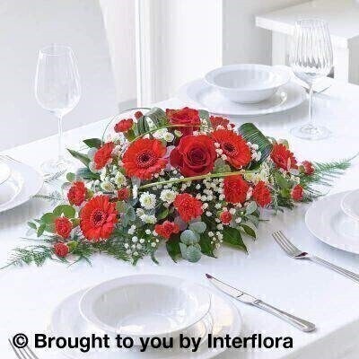 Red Flowers – Table Centrepiece <br><br> Liverpool Flower Delivery<br><br> We offer advanced booking flower delivery same day flower delivery 3 hour Flower delivery guaranteed AM PM or Evening Flower Delivery and we are now offering Sunday Flower Delivery. .<br><br> <ul><li>Hand arranged by our florists</li><li> To give the best occasionally we may make substitutes</li><li> Our flowers backed by our 7 days freshness guarantee</li><li> Approximate dimensions 28x17cm</li><li> This product is available for delivery throughout the UK</li></ul><br><br>  THIS ARRANGMENT IS IN FLORAL FOAM AND COMES PRE ARRANGED IN CONTAINER Red roses and red germini create a floral centrepiece bursting with crimson hues. The beautiful blooms in shades of red are mixed with greens to create a stunning table centre and is perfect for adding a touch of drama to your table.<br><br>  Featuring 5 red germini  2 large-headed red roses  4 red spray carnations  3 green spray chrysanthemums arranged with asparagus fern  aspidistra and aralia  steel grass and eucalyptus.<br><br> The best florist in Liverpool<b><b>Come to Booker Flowers and Gifts Liverpool for your Beautiful Flowers and Plants if you really want to spoil we also have a great range of Wines Champagne Balloons Vases and Chocolates that can be delivered with your flowers. To see the full range see our extras section. You can trust Booker Flowers and Gifts can deliver the very best for you