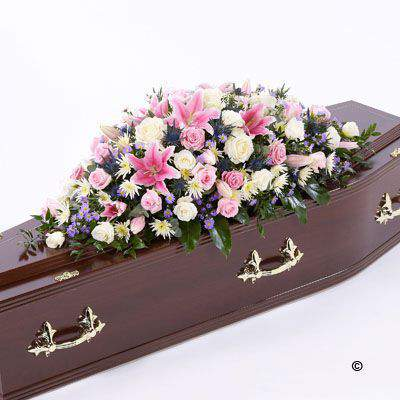A selection of pink and white Rose are arranged with stunning pink Oriental Lily - blue eryngium - white spray chrysanthemums - lilac September flowers and a selection of foliage to create this beautiful casket spray.