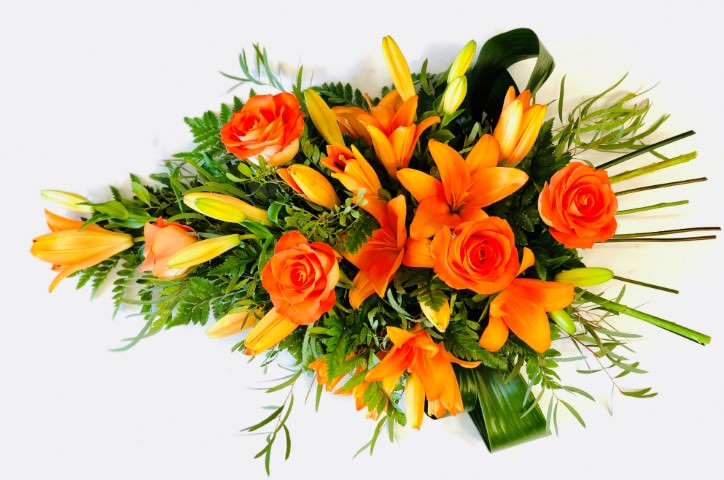 Aralia leaves and French ruscus are nestled amongst classic orange Oriental Lily and orange large-headed roses in this classic teardrop spray.