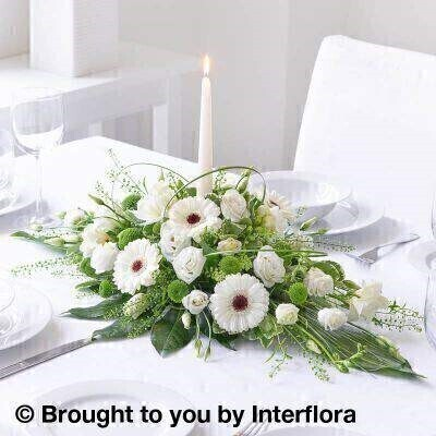 White Flowers – Table Centrepiece <br><br> Liverpool Flower Delivery<br><br> We offer advanced booking flower delivery same day flower delivery 3 hour Flower delivery guaranteed AM PM or Evening Flower Delivery and we are now offering Sunday Flower Delivery. .<br><br> <ul><li>Hand arranged by our florists</li><li> To give the best occasionally we may make substitutes</li><li> Our flowers backed by our 7 days freshness guarantee</li><li> Approximate dimensions 70x35cm</li><li> This product is available for delivery throughout the UK</li></ul><br><br>  THIS ARRANGMENT IS IN FLORAL FOAM AND COMES PRE ARRANGED IN CONTAINER Germini  lisianthus and fragrant freesia  all in pristine white  combine to create this classic yet timeless centrepiece. A tall  elegant candle makes a charming finishing touch.<br><br>  Featuring 3 white double lisianthus  4 white freesia  6 white germini and a green spray chrysanthemum arranged with thlaspi  aralia and aspidistra leaves  pittosporum and steel grass and a tall ivory tapered candle in the centre.<br><br> The best florist in Liverpool<b><b>Come to Booker Flowers and Gifts Liverpool for your Beautiful Flowers and Plants if you really want to spoil we also have a great range of Wines Champagne Balloons Vases and Chocolates that can be delivered with your flowers. To see the full range see our extras section. You can trust Booker Flowers and Gifts can deliver the very best for you