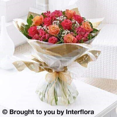 This very individual design reflects the many shades of a summer sunset – think how warm gold turns to peach and deeper pink tones… The combination of luxurious fresh roses with delicate alstroemeria and a dusting of gypsophila makes a truly stunning hand-tied bouquet.<br><br> Featuring peachy pink large headed roses  cerise alstroemeria and cerise large headed roses with white gypsophila and salal  wrapped and trimmed with a gold voile ribbon and presented in Interflora Gift Packaging.