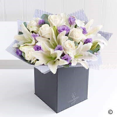 This elegant and effortlessly beautiful Vera Wang bouquet celebrates the much loved combination of roses and lilies. The serene blanket of cream is only broken by the flashes of purple from the carefully interspersed lilac lisianthus - and the glorious scent from the Oriental lilies is the perfect finishing touch. Just exquisite.Featuring Ice Bear cream roses and white Oriental lilies expertly hand-tied with lilac lisianthus - and finished with luxurious Vera Wang gift wrapping.