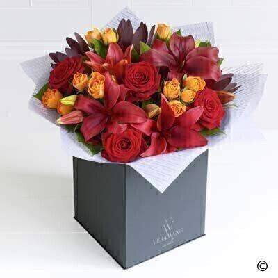 A celebration of the warmest - most vibrant natural colours - this magnificent Vera Wang bouquet is a striking statement piece. The scarlet - large-headed roses pair with the crimson red Asiatic lilies perfectly. Adding rich burgundy leucadendron and orange spray roses creates a vibrant mix of colour and a very opulent gift.Featuring Grand Prix red roses - Abeba orange spray roses - dark red leucadendron and red Asiatic lilies expertly hand-tied with salal - and finished with luxurious Vera Wang gift wrapping.