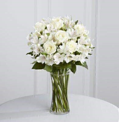 Pure white roses and alstroemeria are accented by lush greens and beautifully arranged in a clear curved glass vase to create an elegant gift that is ready to display straight away.