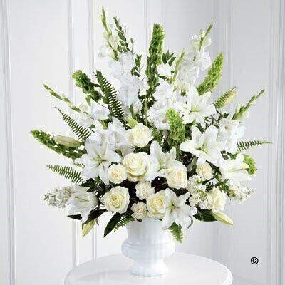 This stunning urn arrangment is a beautiful expression of peace and soft serenity. White roses - carnations - gladioli - stocks and Oriental Lily are accented with the bright green Stems of molucella and an assortment of foliage.
